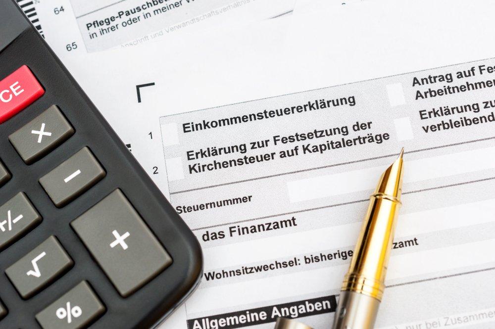Einkommensteuererklärungsantrag mit Taschenrechner und Stift