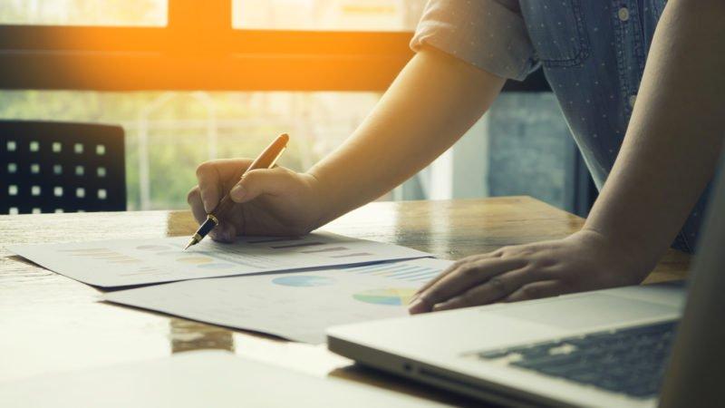 Mann wertet Statistiken aus und schreibt Businessplan
