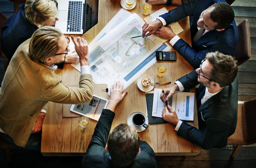 Jungunternehmer sitzen gemeinsam am Tisch und beraten über Unternehmenszukunft
