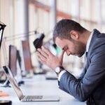 Gescheiterter Unternehmer hält sich den Kopf auf Schreibtisch