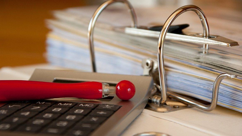 Taschenrechner liegt mit rotem Stift auf Aktenordner